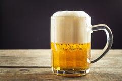 倾吐的啤酒到在一张木桌上的一块玻璃里 酒精饮料 无酒精啤酒 啤酒销售对酒吧 库存照片