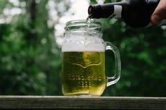 倾吐的啤酒到瓶子里外面 免版税图库摄影