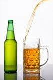 倾吐的啤酒到杯子里 免版税库存照片