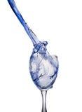 倾吐的明亮的蓝色液体小河飞溅入一个清楚的酒杯,在干净的白色背景 库存图片