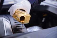 倾吐的机器润滑油到发动机里 免版税库存图片