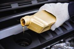 倾吐的机器润滑油到发动机里 免版税图库摄影