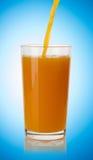 倾吐的橙汁到玻璃里 免版税库存图片