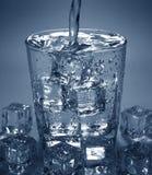 倾吐的水喝入与冰块的玻璃 免版税库存照片