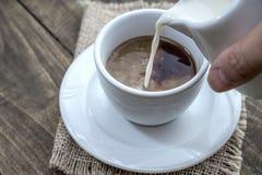 倾吐的牛奶到一杯咖啡里 免版税库存图片