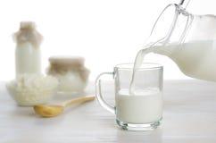 倾吐的牛奶到在乳制品背景的玻璃里 免版税库存图片