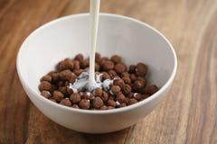 倾吐的牛奶到巧克力在白色碗的谷物球里在木桌上的早餐 图库摄影