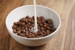 倾吐的牛奶到巧克力在白色碗的谷物球里在木桌上的早餐 库存图片