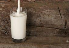 倾吐的牛奶到高玻璃里 免版税图库摄影