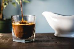 倾吐的牛奶和咖啡在玻璃 免版税库存照片