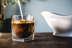 倾吐的牛奶和咖啡在玻璃 免版税图库摄影