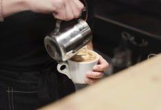 倾吐的牛奶咖啡barista热奶咖啡投手 库存照片