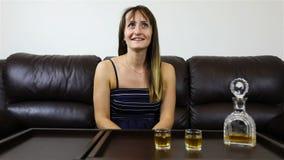 倾吐的科涅克白兰地到玻璃,一个对客人的好的女孩谈话里 股票录像