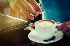倾吐的糖浆到拿铁热的咖啡杯 库存照片