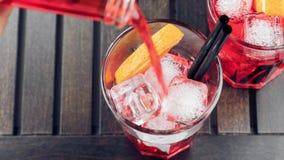 倾吐的红色看法上面喷开胃酒与橙色切片和冰块的aperol鸡尾酒 股票视频