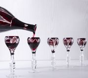 倾吐的红色酒到葡萄酒玻璃器皿里,自助餐晚餐 开胃酒的概念 免版税库存图片