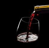 倾吐的红葡萄酒到反对黑背景的玻璃里 免版税库存照片