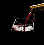 倾吐的红葡萄酒到反对黑背景的玻璃里 免版税库存图片