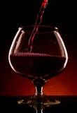倾吐的红葡萄酒到玻璃里 免版税库存照片