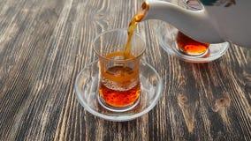 倾吐的茶到在一张木桌上的一个杯子里 影视素材