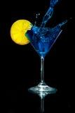 倾吐的蓝色马蒂尼鸡尾酒到马蒂尼鸡尾酒玻璃里用柠檬 免版税图库摄影