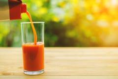 倾吐的西红柿汁到在木桌上的一块玻璃里 库存照片