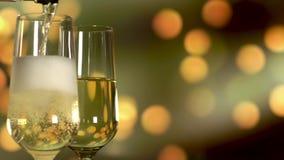 倾吐的闪耀的香槟到在金黄假日眨眼睛背景的玻璃里 股票录像