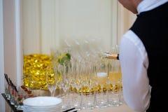 倾吐的香槟到在一个欢乐事件的一块玻璃里 免版税库存图片