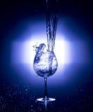 倾吐的水到与黑背景蓝色白色平衡的酒杯里 免版税库存图片