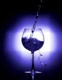 倾吐的水到与黑背景蓝色白色平衡的酒杯里 免版税图库摄影