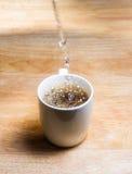 倾吐的水到咖啡在木桌上的里 在飞溅水的焦点 库存图片