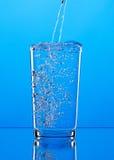 倾吐的水到在蓝色背景的玻璃里 免版税库存图片