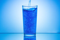 倾吐的水到在蓝色背景的玻璃里 免版税库存照片
