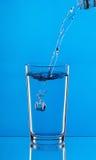 倾吐的水到在蓝色背景的玻璃里 库存照片