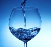 倾吐的水到玻璃里 免版税库存照片