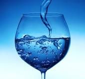 倾吐的水到玻璃里 免版税库存图片