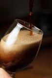 倾吐的黑啤酒 库存图片