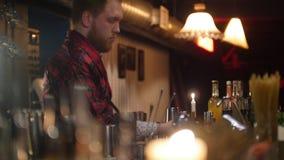 倾吐红色饮料的年轻专业侍酒者入在酒吧的玻璃与软的内景照明 股票录像