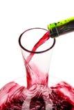 倾吐蒸馏瓶的红葡萄酒 免版税库存图片