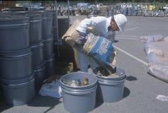 倾吐袋子的内容的工作者入一个容器废料在世界地球日的废清洁站点在优尼科植物 免版税库存照片