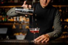 倾吐酒精饮料用从振动器的堪蓓莉开胃酒的男服务员入鸡尾酒杯 免版税图库摄影