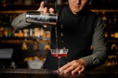 倾吐酒精饮料用堪蓓莉开胃酒的男服务员入鸡尾酒杯 免版税库存照片