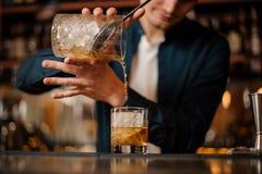 倾吐酒精饮料的深色的侍酒者入与一个大冰块的一块玻璃 图库摄影