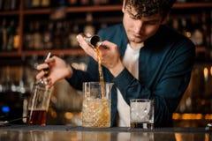 倾吐酒精饮料的深色的侍酒者入与冰的玻璃 库存照片