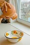 倾吐陶瓷大口水罐油的女性手入金属碗 绘在白色搪瓷,棕色陶器水罐特写镜头垂直 库存图片