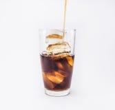 倾吐从塑料瓶的软饮料入被填装的玻璃 免版税图库摄影