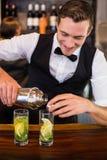 倾吐从振动器的侍酒者一份饮料到在酒吧柜台的一块玻璃 免版税库存照片