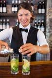 倾吐从振动器的侍酒者画象一份饮料到在酒吧柜台的一块玻璃 库存图片
