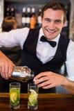 倾吐从振动器的侍酒者画象一份饮料到在酒吧柜台的一块玻璃 免版税库存照片
