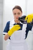 倾吐洗涤剂的年轻管家 免版税图库摄影